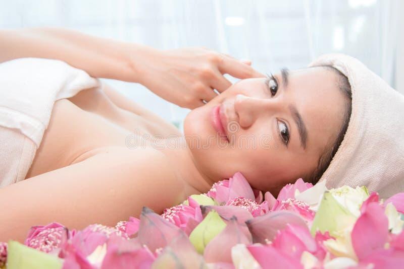 Détendez la femme dans le salon de station thermale se trouvant sur le bureau de massage photo stock