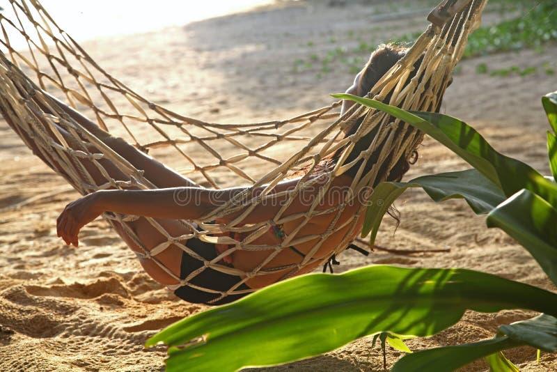 Détendez la femme heureuse sur lever de soleil de coucher du soleil de fond de plage de berceau ou d'hamac le beau image stock