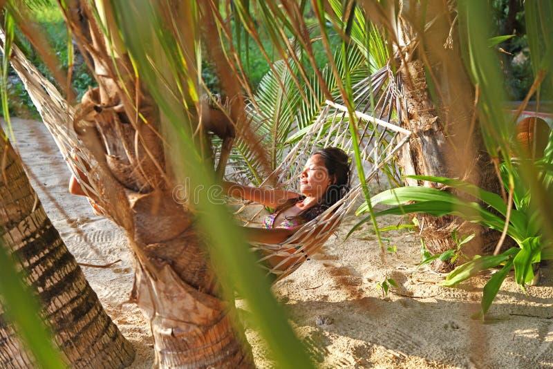 Détendez la femme heureuse sur lever de soleil et la noix de coco de coucher du soleil de fond de plage de berceau ou d'hamac le  photo stock