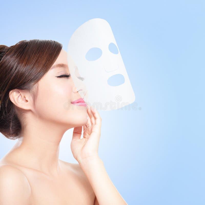 Détendez la jeune femme avec le masque de massage facial de tissu photos libres de droits