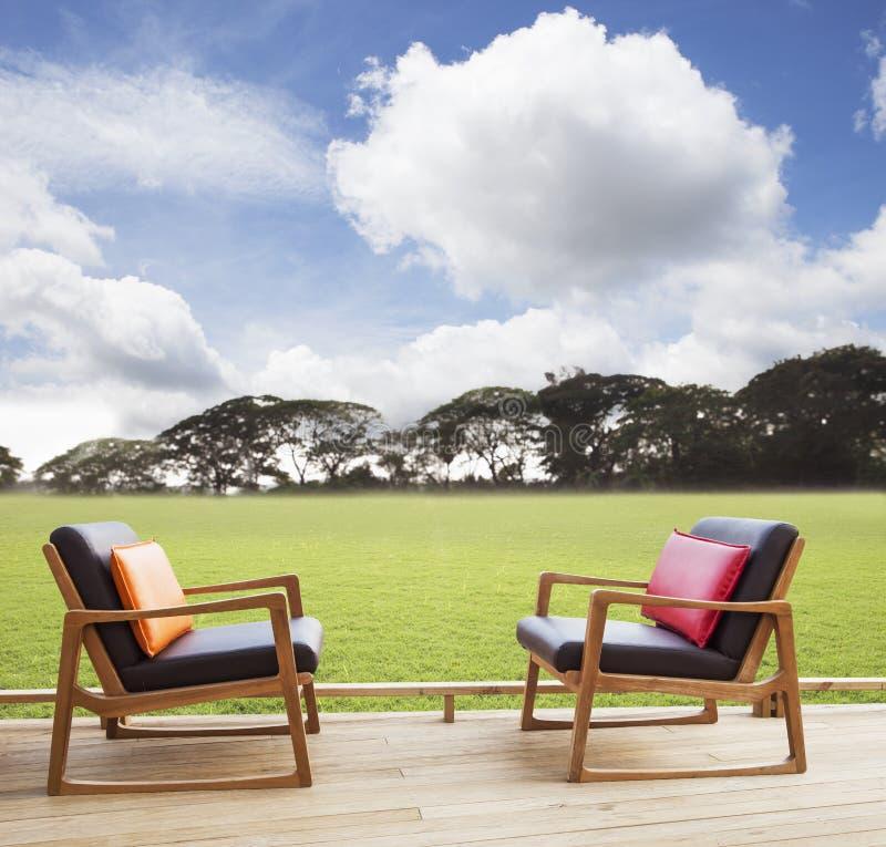 Détendez les chaises sur la terrasse en bois avec le champ d'herbe et le beau ciel photos stock