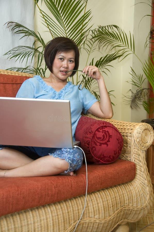 Détente à la maison avec l'ordinateur image stock