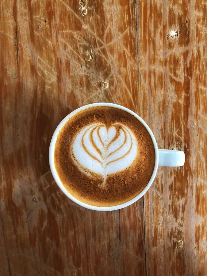 Détente avec du café d'art de Latte dans la tasse en céramique blanche photos stock