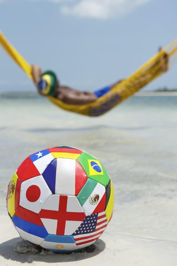 Détente brésilienne avec le football du football dans l'hamac de plage image libre de droits