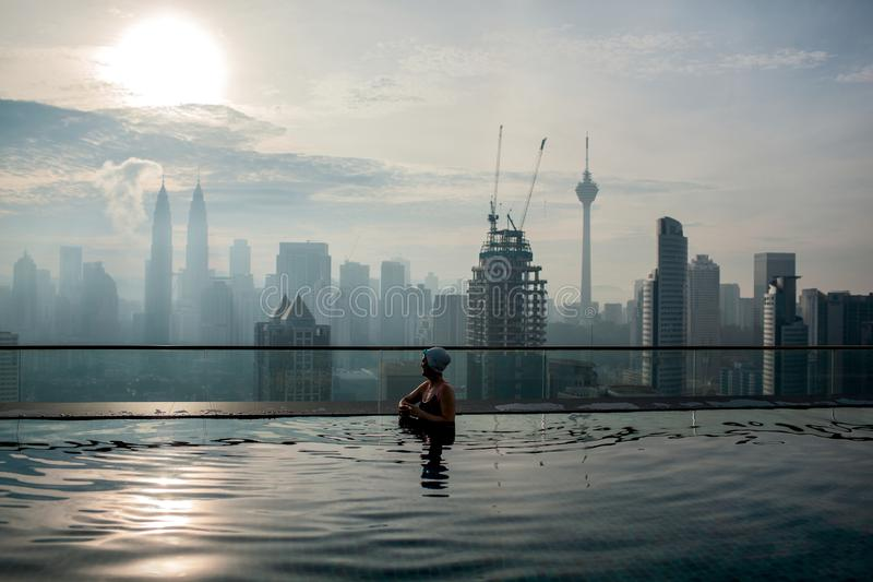 Détente dans la piscine et apprécier le panorama de ville Kuala Lumpur, Malaisie images stock