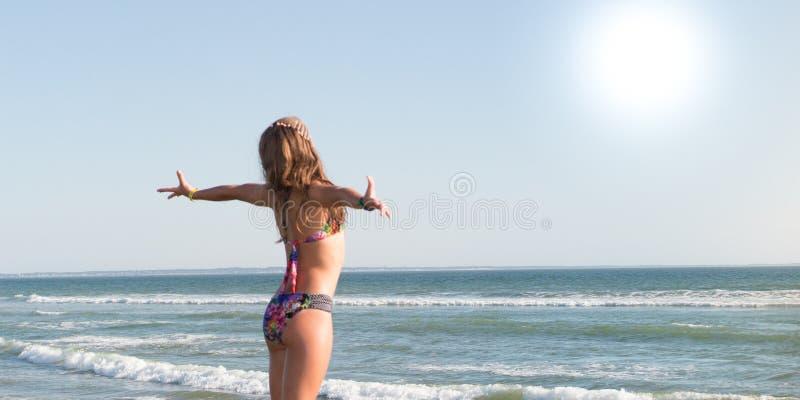 Détente de bronzage du soleil de femme de corps de bikini sur l'eau tropicale parfaite d'océan de plage et de turquoise dans des  image stock