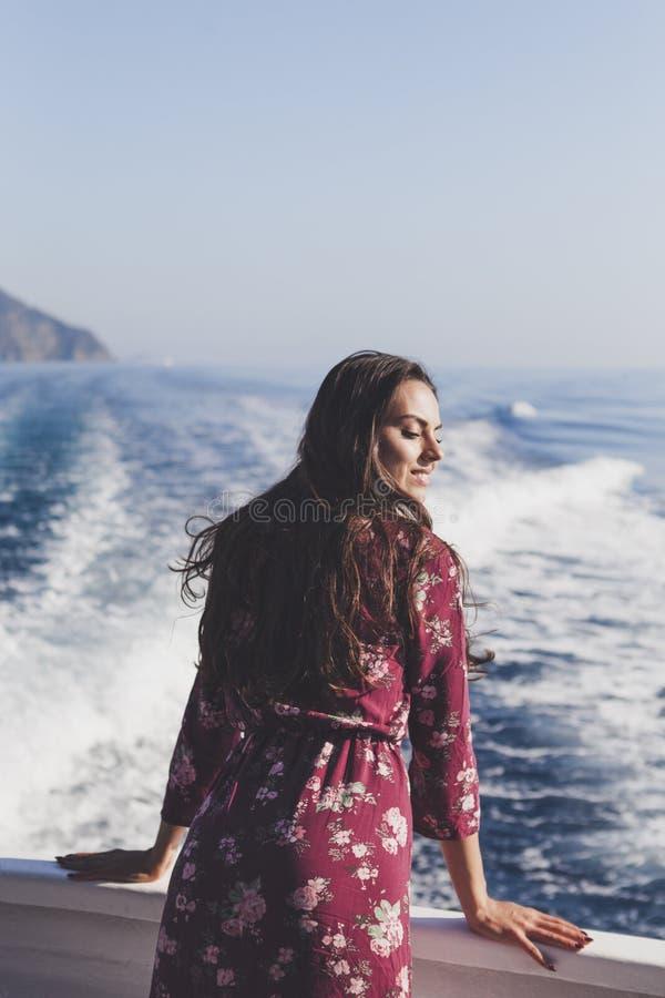Détente de port de jeune femme étonnante heureuse sur le yacht dans Cinq image libre de droits