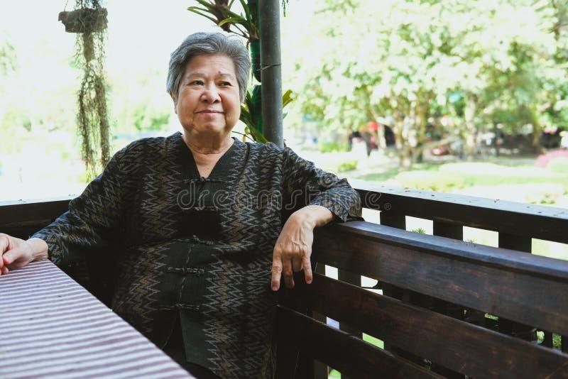 détente de sourire de vieille femme agée à la maison séance supérieure d'aîné heureux sur la terrasse image stock