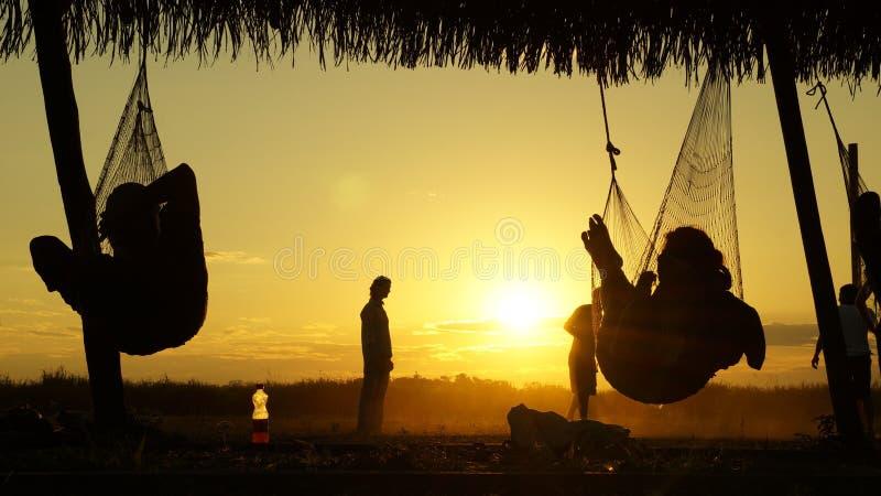 Détente de touristes dans des hamacs pendant le coucher du soleil au parc national de Madidi en Bolivie photographie stock