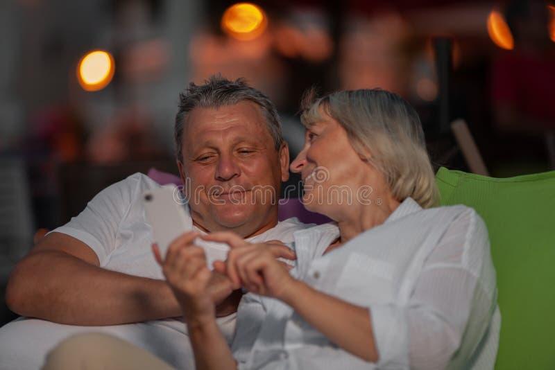 Détente mûre gaie de couples extérieure et regard par les photos mobiles photographie stock