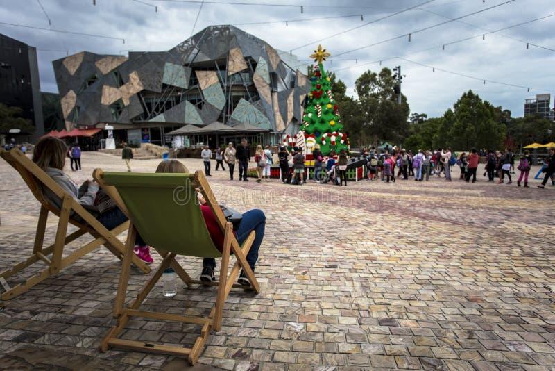 Détente sur la chaise paresseuse par la place Melbourne Victoria Australia de fédération image stock