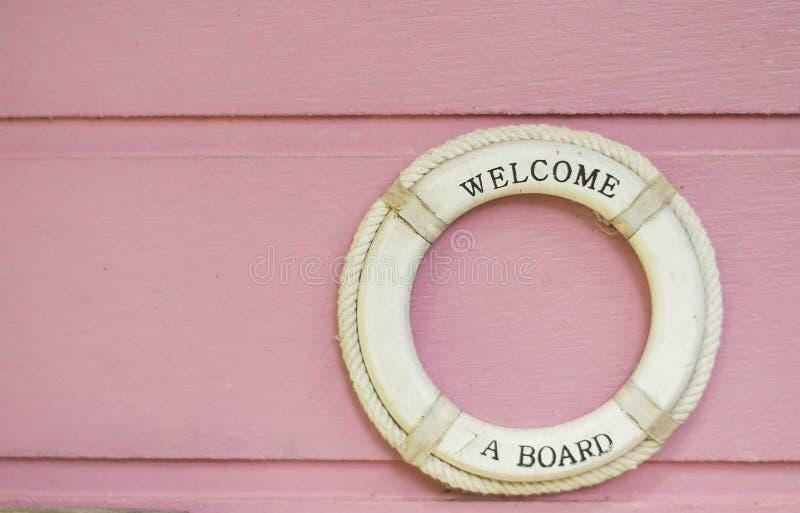 Dê boas-vindas a uma correia de vida branca da placa no fundo de madeira cor-de-rosa imagem de stock