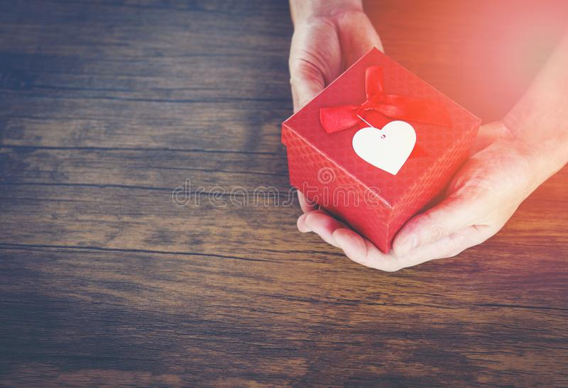 Dê o homem do amor que guarda a caixa atual vermelha pequena nas mãos com coração para o dia de Valentim do amor que dá uma caixa imagem de stock royalty free