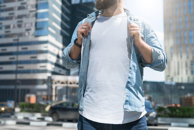 Día asoleado del verano El hombre barbudo del inconformista se vistió en la camiseta blanca, camisa azul del dril de algodón, sop fotografía de archivo libre de regalías