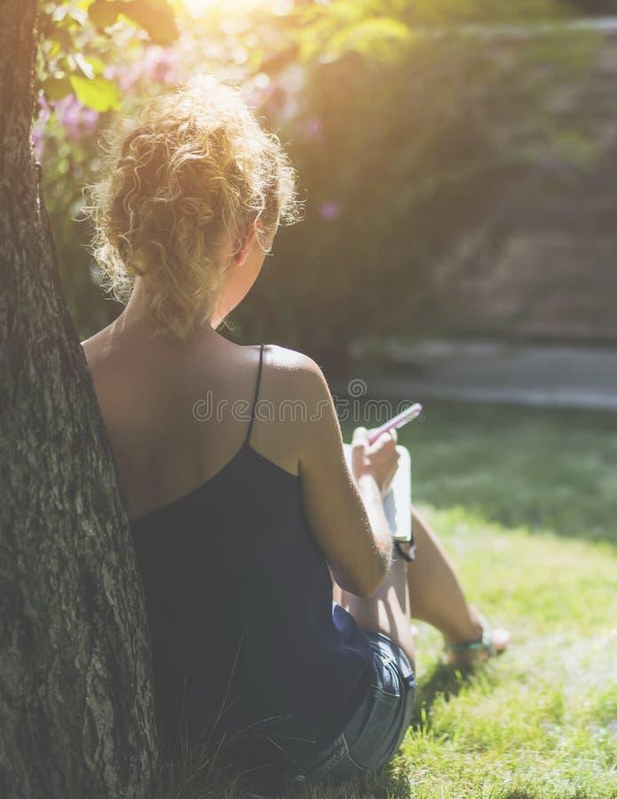 Día asoleado del verano Visión posterior La mujer joven se sienta en un parque debajo de árbol en un césped y hace notas en un cu fotografía de archivo