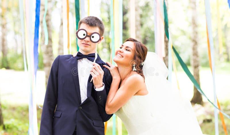 Día de April Fools ' Los pares de la boda se divierten con la máscara fotografía de archivo