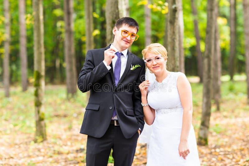Día de April Fools ' Pares que presentan con los labios del palillo, máscara de la boda foto de archivo libre de regalías