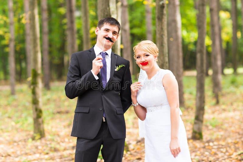 Día de April Fools ' Pares que presentan con los labios del palillo, máscara de la boda imágenes de archivo libres de regalías