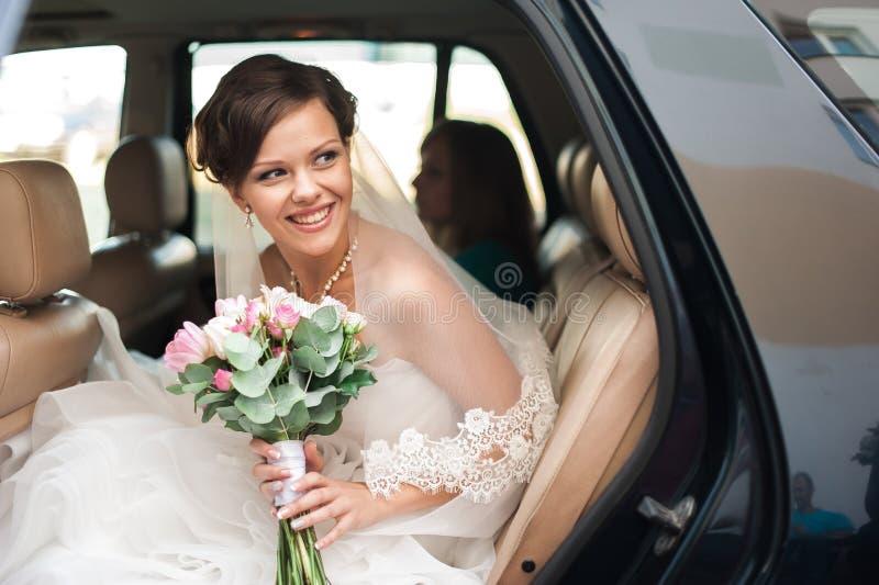 Día de boda La novia es que se sienta y sonriente en un coche con la boda foto de archivo