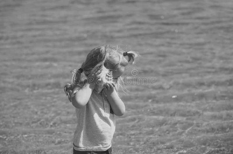 Día de fiesta del ` s de los niños El muchacho escucha la cáscara en la playa del mar imagen de archivo libre de regalías