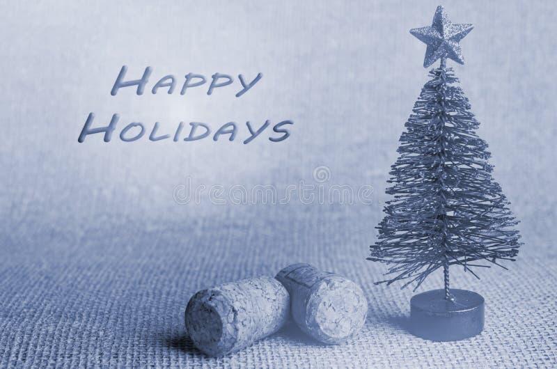 Día de fiesta feliz escrito adentro Árbol de navidad artificial con el corcho del champán en fondo gris fotografía de archivo libre de regalías