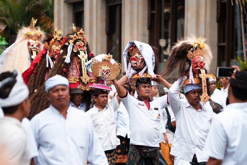 Día de fiesta de Galungan Hombres en la ropa blanca en una procesión festiva con las estatuas de deidades en sus cabezas Isla de  imagen de archivo