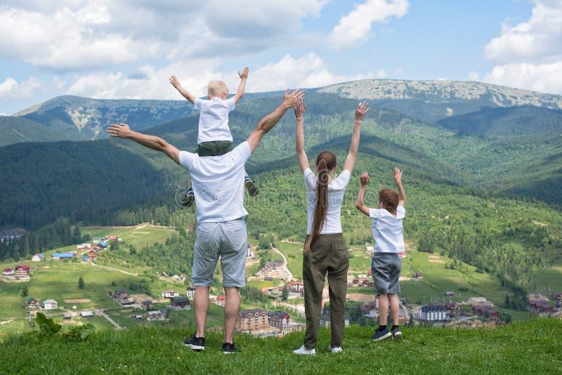 Día de fiesta de la familia Los padres y los niños se colocan con sus manos para arriba imagen de archivo