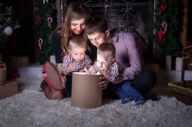 Día de fiesta de la Navidad La familia abre la caja mágica con el regalo fotos de archivo