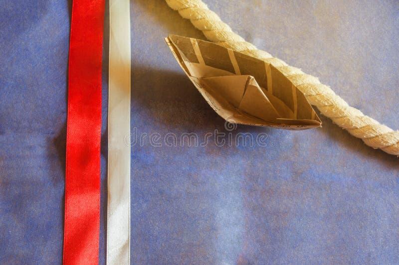 Día de fiesta de los E.E.U.U., barco feliz del papel de Columbus Day en fondo azul y decoración de la cinta, LUZ SOLAR imagenes de archivo
