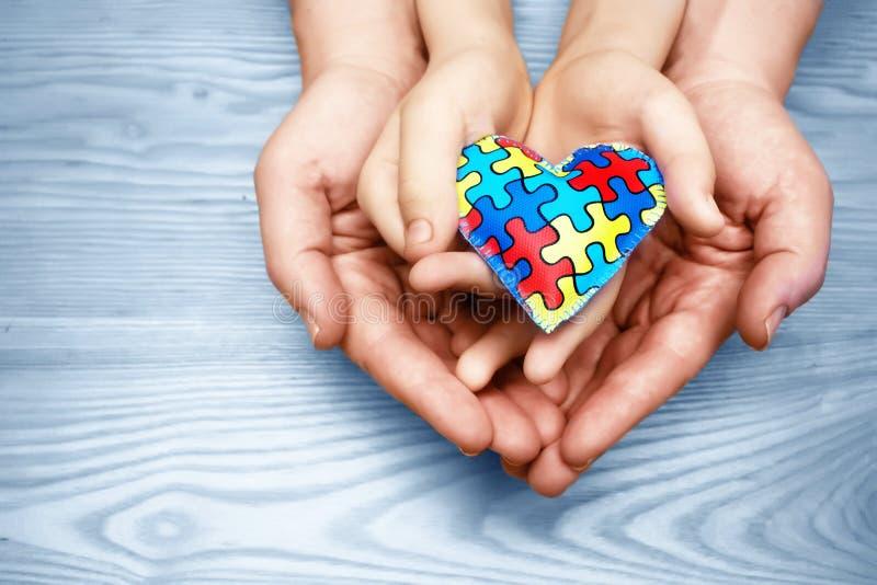 Día de la conciencia del autismo del mundo, rompecabezas o modelo del rompecabezas en corazón con las manos autísticas del niño y imagen de archivo libre de regalías