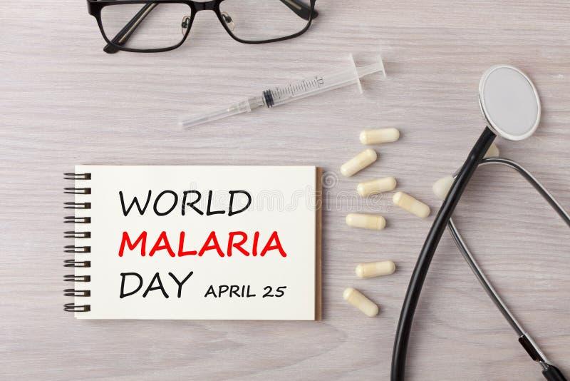 Día de la malaria del mundo escrito en concepto del cuaderno imágenes de archivo libres de regalías
