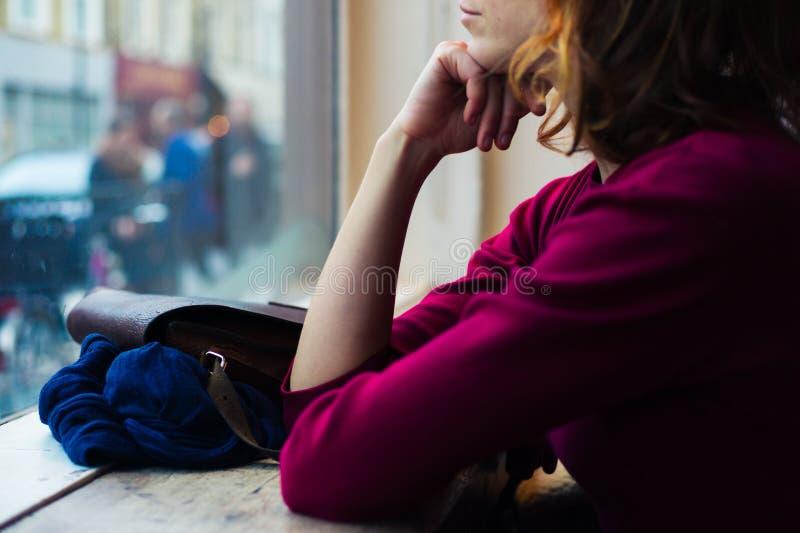 Día de la mujer joven que sueña por la ventana fotos de archivo