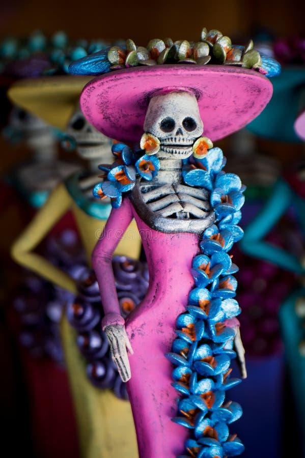 Día de los muertos Figurilla de una mujer - esqueleto femenino con un dredd rosado imagenes de archivo