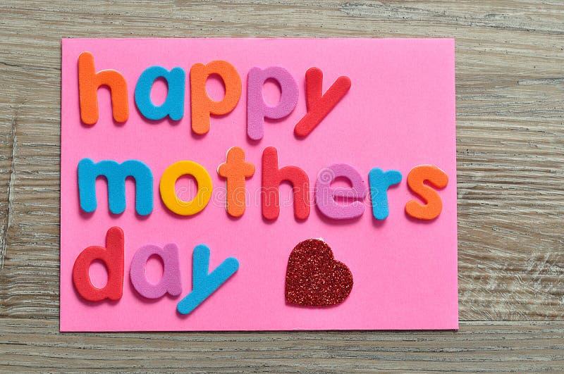 Día de madres feliz en una nota rosada con un corazón rojo fotografía de archivo libre de regalías