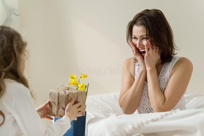 Día de madres La pequeña hija guarda un regalo y las flores para su madre Interior del fondo del dormitorio, madre en la cama, ma imagen de archivo libre de regalías