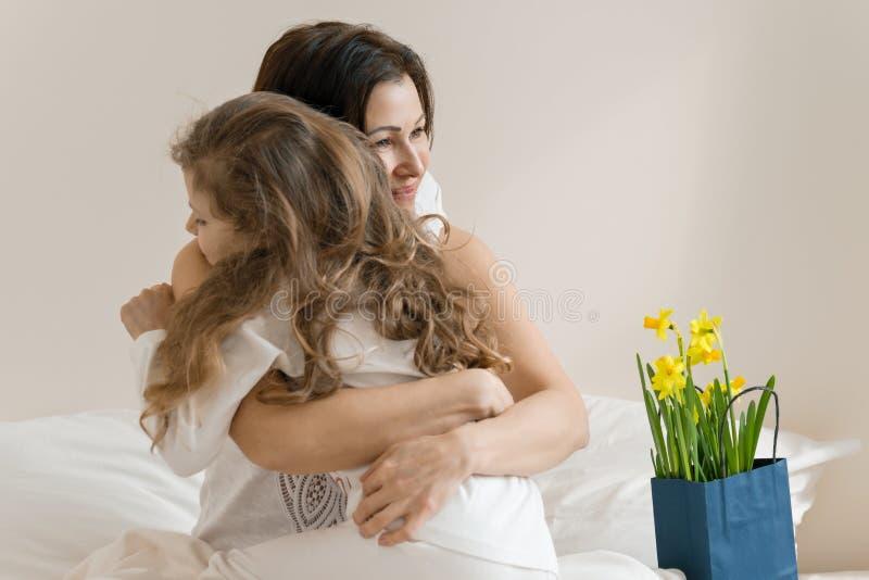 Día de madres Mañana, mamá y niño en cama, madre que abraza a su pequeña hija Interior del fondo del dormitorio, ramo de flores imagen de archivo