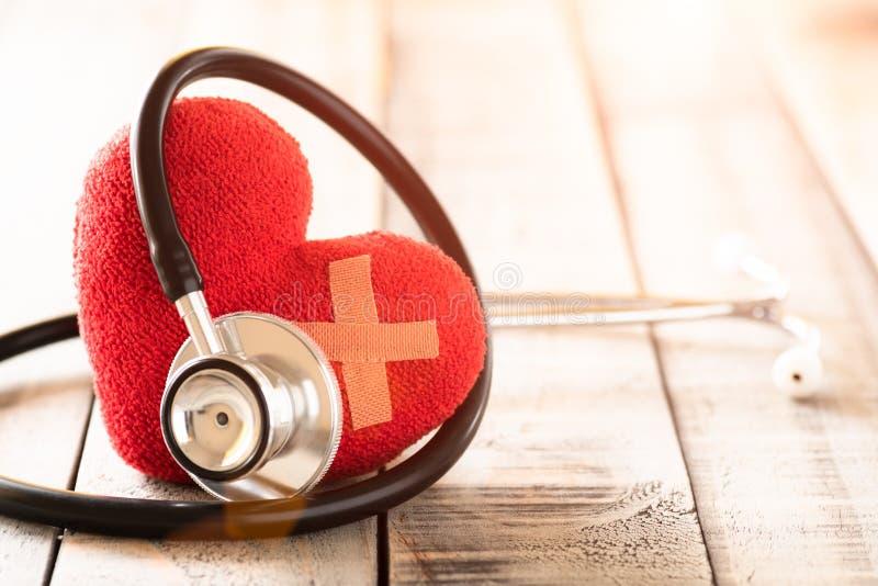 Día de salud de mundo, atención sanitaria y concepto médico Corazón rojo con el estetoscopio en textura de madera del fondo de la imagen de archivo libre de regalías