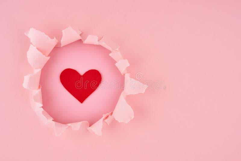 Día de San Valentín Un agujero y un corazón rojo con fondo de textura rosa brillante, concepto de papel roto con espacio de copia imagenes de archivo