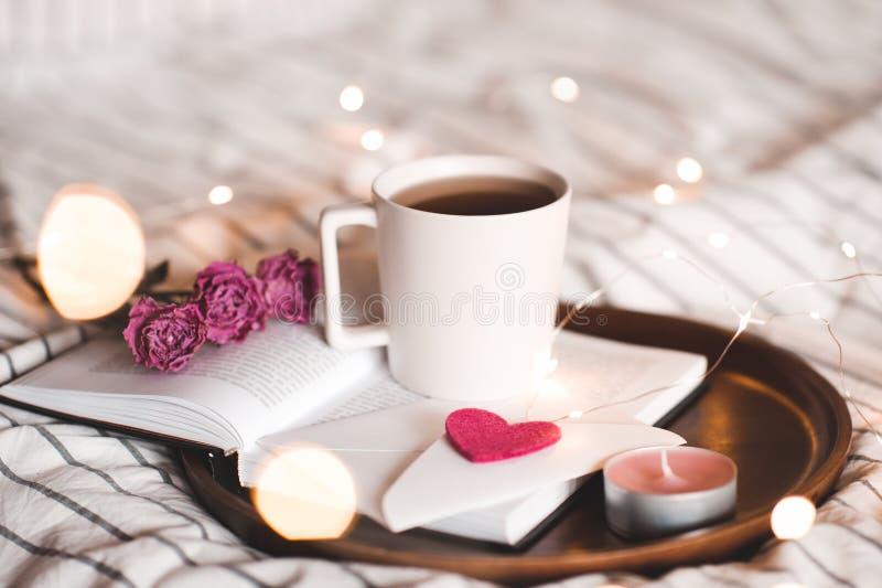 Día de tarjetas del día de San Valentín con la taza de té en cama fotos de archivo libres de regalías