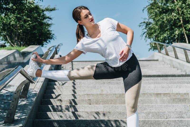 Día de verano asoleado Mujer joven que hace estirando los ejercicios al aire libre Muchacha que hace calentamiento en pasos antes imagen de archivo libre de regalías