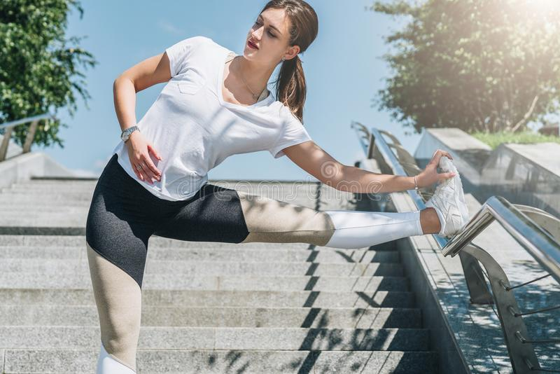 Día de verano asoleado Mujer joven que hace estirando los ejercicios al aire libre Muchacha que hace calentamiento en pasos antes foto de archivo