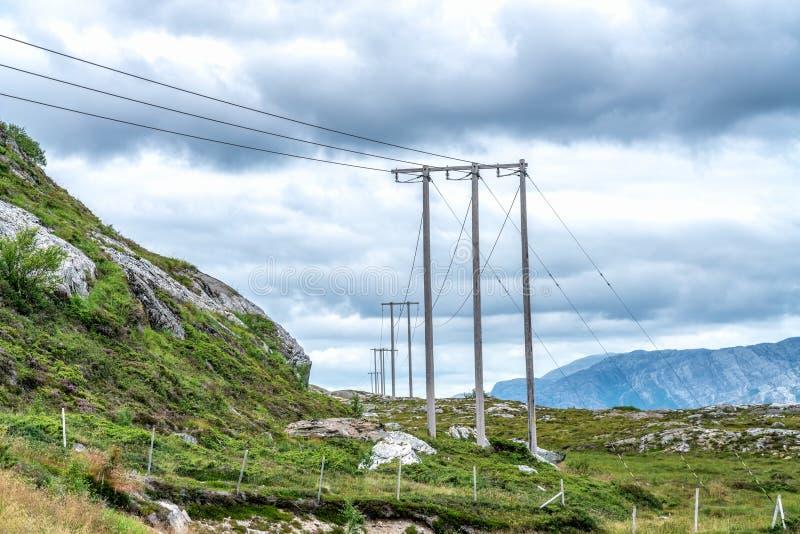 Día de verano, nubes justo encima de las montañas en el norte de Noruega La línea de energía pasa por las montañas fotografía de archivo