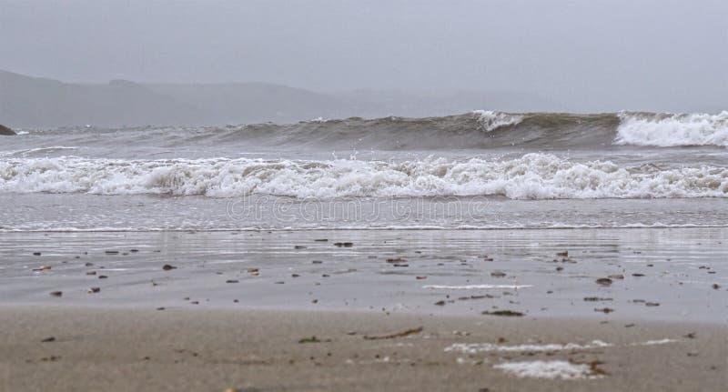 Día de verano tempestuoso cubierto en la playa en Cornualles del sur, Reino Unido foto de archivo