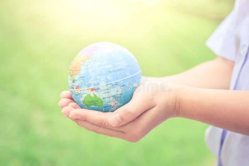 Día del ambiente mundial, manos del niño que llevan a cabo el concepto de la tierra para cuidar el planeta o ahorrar concepto de  imagen de archivo libre de regalías