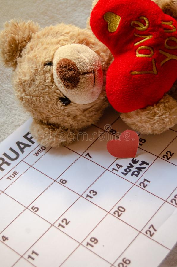 Día del amor - corazones rojos de papel que marcan el 14 de febrero día de San Valentín en el calendario blanco con el oso de pel fotografía de archivo