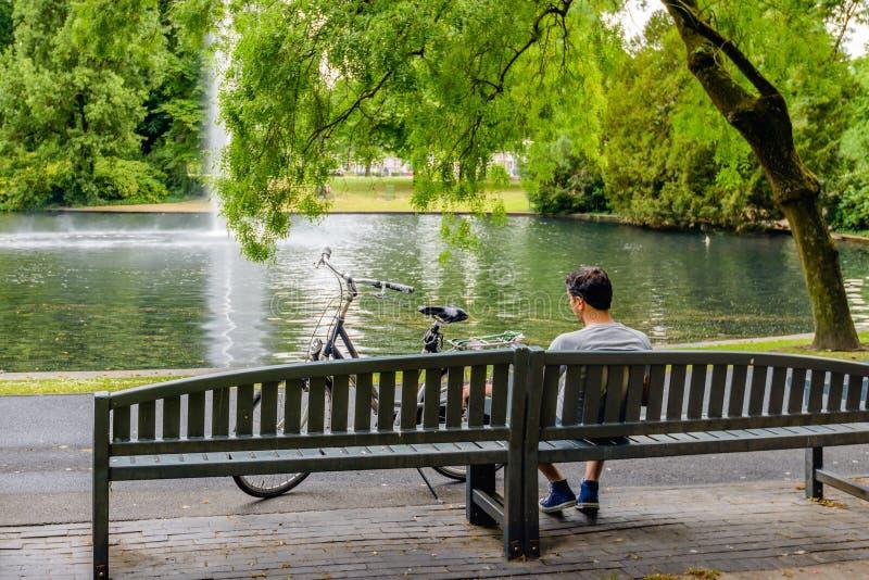Día del hombre joven que sueña en un banco de madera en el parque foto de archivo libre de regalías