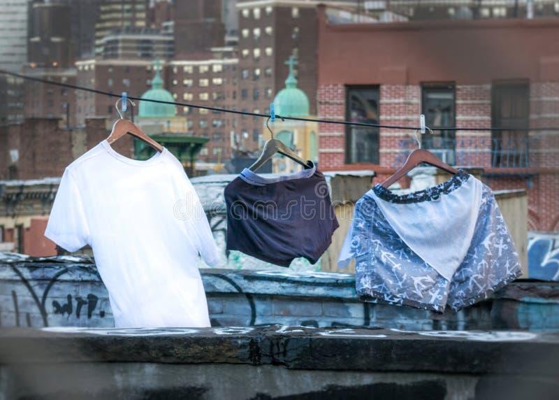 Día del lavadero en New York City, ropa que se seca en un tejado de Manhattan, entre pintada y rascacielos, primer fotografía de archivo