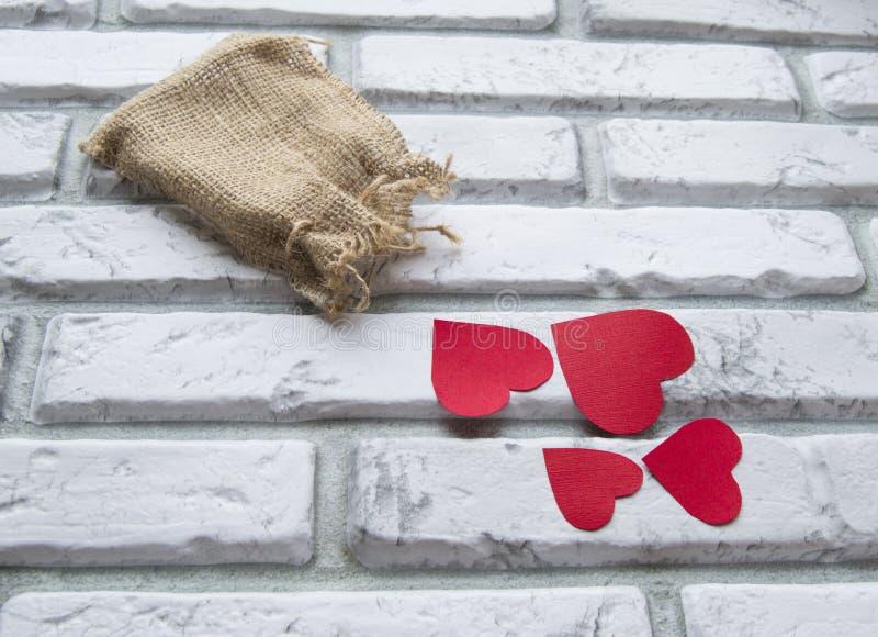 Día del ` s de la tarjeta del día de San Valentín, bolso rojo de la lona de los corazones, pared de ladrillo del blanco del fondo imagen de archivo