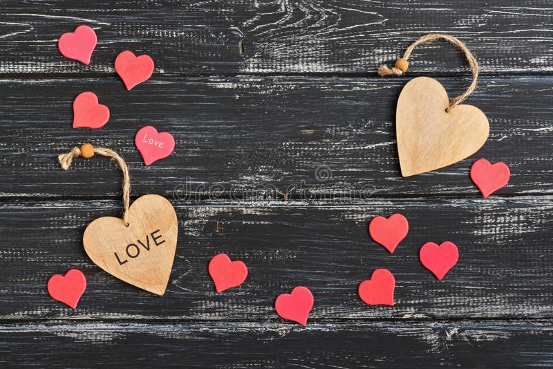 Día del ` s de la tarjeta del día de San Valentín, dos corazones de madera rodeados por un pequeño corazón rojo en un fondo de ma fotos de archivo libres de regalías