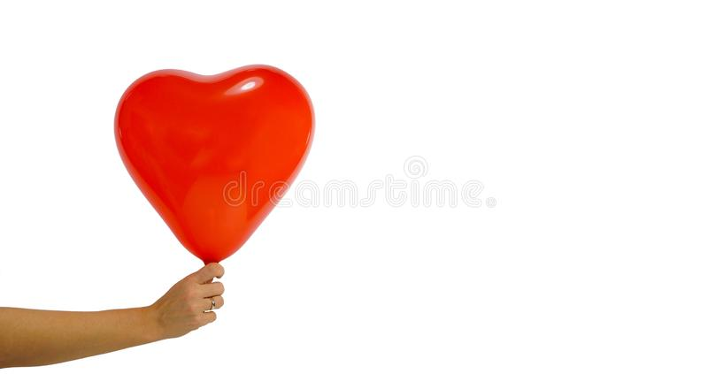 Día del `s de la tarjeta del día de San Valentín Un globo grande en la forma de un corazón llevado a cabo en la mano de una mujer fotografía de archivo libre de regalías
